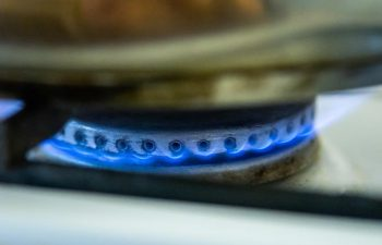 Burning gas of a kitchen stove. Blue fire under iron pot.